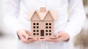 Immobilienkonzept - eine Frau hält ein Architekturmodell eines Hauses lizenzfreie stockfotos