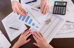 Immobilienmakler, der die Abnahme von Zinssätzen zeigt Lizenzfreie Stockfotos