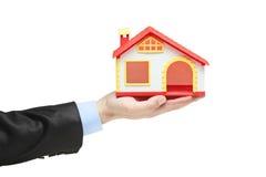 Immobilienmakler, der ein vorbildliches Haus in einer Hand anhält Stockfotos