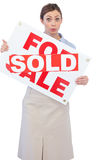 Immobilienmakler, der für Verkaufszeichen mit Verkaufsaufkleber über ihm darstellt Lizenzfreie Stockfotografie