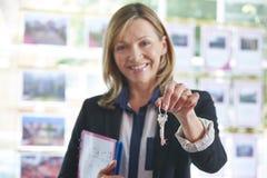 Immobilienmakler-In Office Holding-Schlüssel zum Eigentum Stockbilder