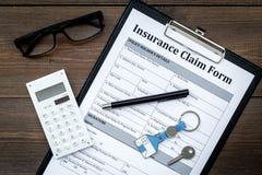 Immobilienversicherung Anspruch auf Versicherungsleistungen Form nahe Haus keychain auf Draufsicht des dunklen hölzernen Hintergr stockfotos