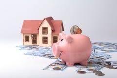 Immobiliers ou économie à la maison tirelire avec des pièces de monnaie sur l'argent et la maison de fond de tache floue photo stock