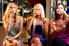 Immodest girls. Three young girls drinking vodka at bar Royalty Free Stock Images