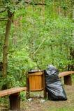 Immondizia in contenitore in foresta Immagini Stock