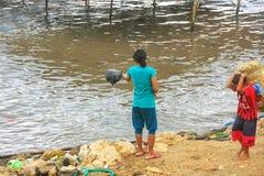 Immondizia di lancio della donna locale nel mare nella città di Labuan Bajo, Flo immagini stock
