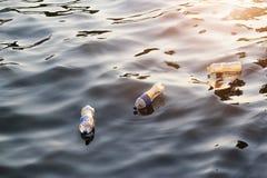 Immondizia di plastica nel fiume sul tramonto, concetto dell'ambiente fotografie stock