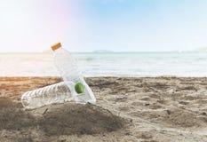 Immondizia nel mare con la bottiglia di plastica sul mare sporco sabbioso della spiaggia sull'isola - problema ambientale di inqu immagini stock