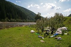 Immondizia sulla sponda del fiume nelle montagne fotografia stock libera da diritti