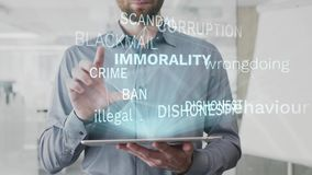 Immorality, behaviour, asocial, illegal, dishonest word cloud made as hologram used on tablet by bearded man, also used stock footage