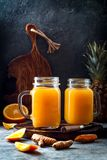 Immune boosting, anti inflammatory smoothie with orange, pineapple, turmeric. Detox morning juice drink. Clean eating Stock Photos