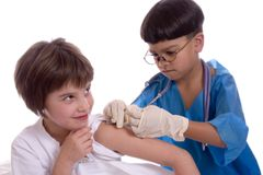 Immunization. Young boy posing as a doctor giving a young girl an immunization Stock Image