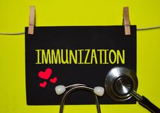 IMMUNIZATION on top of yellow background. A stethoscope and blackboard with word IMMUNIZATION on top of yellow background. Medical, health and education concepts royalty free stock photos