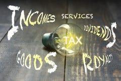 impôt Car une ampoule éclaire sa lumière, des impôts sont imposés aux biens et aux transactions de services, revenus d'entreprise photographie stock libre de droits