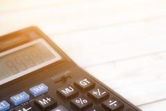 Impôt et bénéfice financiers sur la calculatrice dans le siège social sur le bois De photographie stock