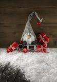Imp divertido en fondo de madera con los regalos de Navidad rojos fotos de archivo