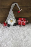 Imp divertido en fondo de madera con los regalos de Navidad rojos Fotografía de archivo libre de regalías