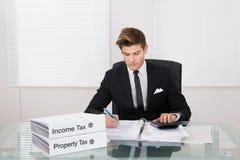 Impôt calculateur d'homme d'affaires dans le bureau Image stock