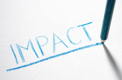Impact. A blue pencil is smash on a piece of paper after writing the word 'IMPACT Stock Photos