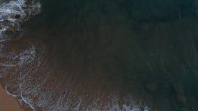 Impacto das ondas em uma praia mesmo após o por do sol vídeos de arquivo