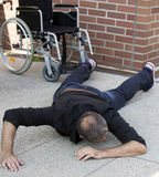 Impaired man on the floor after falling out of wheelchair Stock Photos