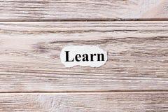 Impari della parola su carta Concetto Parole Learn su un fondo di legno fotografia stock libera da diritti