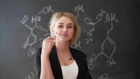 Impari fondo sicuro della lavagna del gesso dell'insegnante della donna di formula di chimica o di scienza il bello stock footage