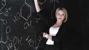 Impari fondo sicuro della lavagna del gesso dell'insegnante della donna di formula di chimica o di scienza il bello video d archivio