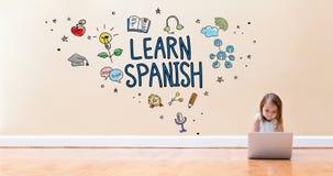 Impari il testo spagnolo con la bambina che per mezzo di un computer portatile fotografie stock