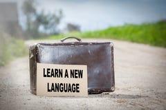 Impari una nuova lingua Vecchia valigia di viaggio sulla strada campestre immagine stock