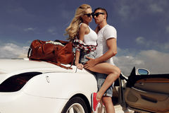 Impassioned couple in casual clothes, posing beside luxurious car Stock Images