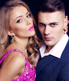 Impassioned couple. handsome businesslike men with beautiful girl with long blond hair. Fashion studio photo of sexy impassioned couple. handsome businesslike Stock Photography