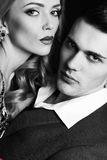 Impassioned couple. handsome businesslike men with beautiful girl with long blond hair. Fashion studio photo of sexy impassioned couple. handsome businesslike Royalty Free Stock Image