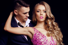 Impassioned couple. handsome businesslike men with beautiful girl with long blond hair. Fashion studio photo of sexy impassioned couple. handsome businesslike Royalty Free Stock Photography