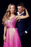 Impassioned couple. handsome businesslike men with beautiful girl with long blond hair. Fashion studio photo of sexy impassioned couple. handsome businesslike Stock Images