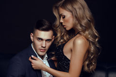Impassioned couple. handsome businesslike men with beautiful girl with long blond hair. Fashion studio photo of sexy impassioned couple. handsome businesslike Royalty Free Stock Photo