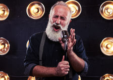 Impassioned man singing in a silver vintage microphone wearing d. Close-up of impassioned man singing in a silver vintage microphone wearing dark shirt and stock photos
