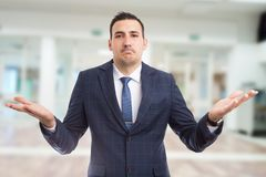 Impassive careless realtor raising hands. On new apartment building lobby background stock image