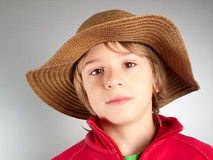 impassive child with straws hat Royalty Free Stock Image