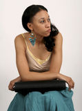 Impatient. Young African-America woman looking impatient as she sits waiting with a portfolio in her lap stock photo