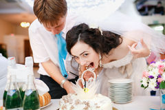 Impatient beautiful bride in white dress leaned. Impatient beautiful bride in a white dress leaned forward quickly and wants to try the wedding cake, groom in a stock image