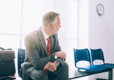 Impatient businessman waiting for a meeting. Impatient businessman waiting for a job interview, he is sitting in the waiting room royalty free stock image