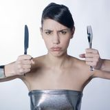 Impatient class woman with silver knife and fork. A studio shot of a  very class woman holding up silver knife and fork with an unhappy expression on face Royalty Free Stock Image
