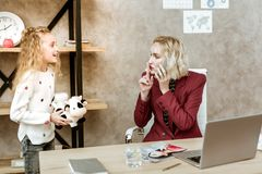 Impatient irritated mother asking her daughter for silence. Busy blonde woman. Impatient irritated mother asking her daughter for silence with finger placed near stock photos