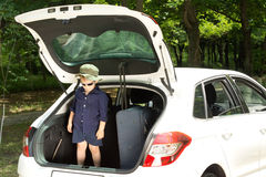 Impatient little boy ready for his vacation. Impatient little boy wearing trendy sunglasses ready for his vacation standing up in the open back of a hatchback royalty free stock photo