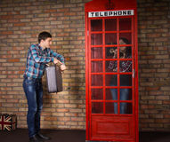 Impatient man pointing to his watch. Impatient men pointing to his watch as he stands alongside a red British telephone booth with his suitcase while his wife royalty free stock photo