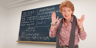 Impatient Maths Teacher. Maths teacher with an impatient gesture with a blackboard as background royalty free stock photos