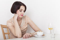 Impatient woman looks at her watch. Sitting in cafeteria having coffee and wine royalty free stock photo