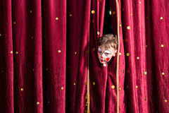 Impatient young actor peeking out from the curtain. Impatient young boy actor wearing colorful red face paint peeking out from the patterned burgundy curtains on stock image