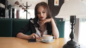 Impatient, young woman looking around and waiting for someone in cafe. Brunette is sitting in a cafe waiting for a. Meeting stock footage